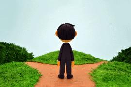 わかれ道に立つ男性の後ろ姿